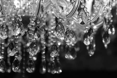 chandeliers: Chrystal chandelier close-up. Glamour black and white background with copy space