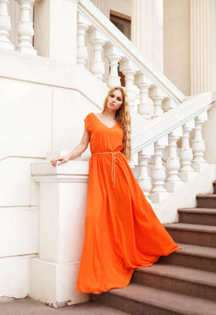 Beautiful blond woman in orange dress outdoors on the stairs