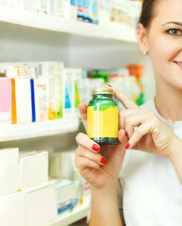 Closeup of a blurred female pharmacist holding out tablets in bottle at drugstore photo