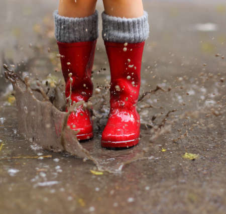 rain wet: Child wearing red rain boots jumping into a puddle. Close up Stock Photo