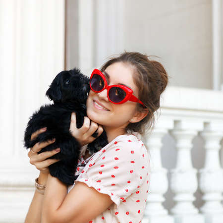 Happy young brunette woman hugging her lap dog puppy photo