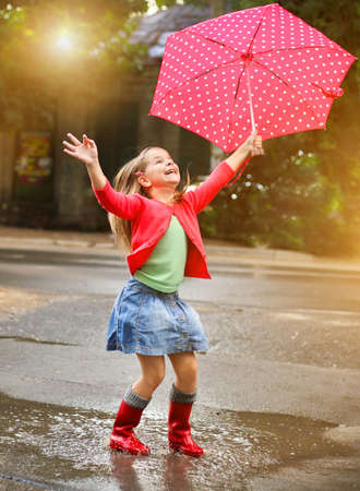 umbrella rain: Child with polka dots umbrella wearing red rain boots jumping into a puddle Stock Photo