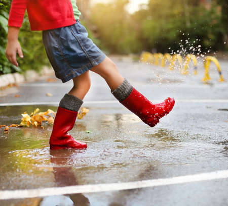 Child wearing red rain boots jumping into a puddle. Close up Фото со стока