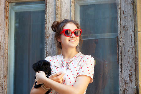 Young brunette woman hugging her lap dog puppy in retro style photo