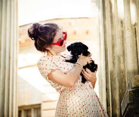 Young brunette woman hugging her lap dog puppy. Retro style photo