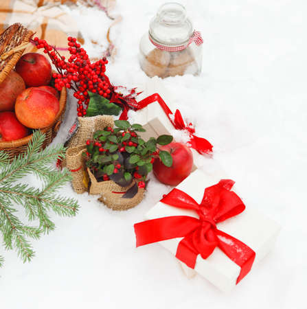 Christmas cookies, apples, presents nestling in fresh snow photo