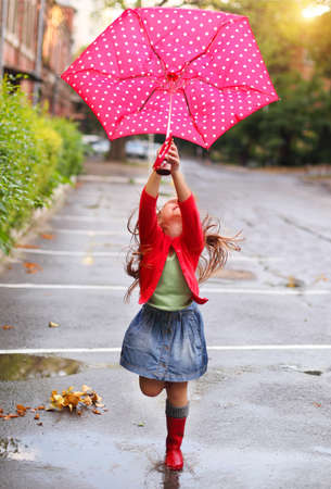 Child with polka dots umbrella wearing red rain boots jumping into a puddle Foto de archivo