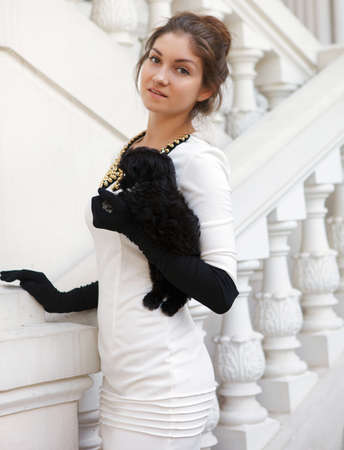 Young brunette woman hugging her lap dog puppy on white stairs photo