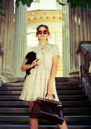 Young brunette woman hugging her lap dog puppy on old stairs photo