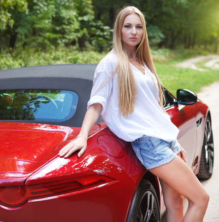 Beautiful blond young woman standing near a  sports car photo