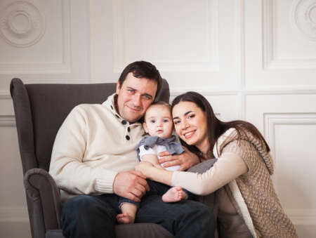Happy smiling family with one year old baby girl indoor photo