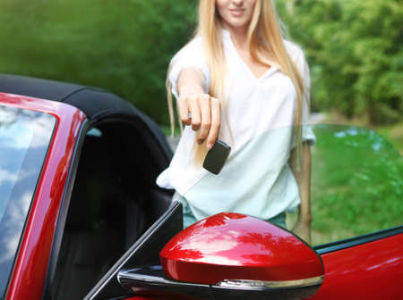 sexy woman car: Happy young blond woman holding keys to her sport car