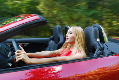 woman driving car: Beautiful blond young woman driving a sports car