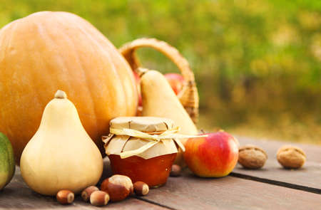 Pumpkins, jam, nuts and basket with apples on garden table photo