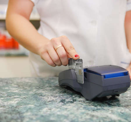 pharm: Close up of human hand putting credit card into payment machine in drug store