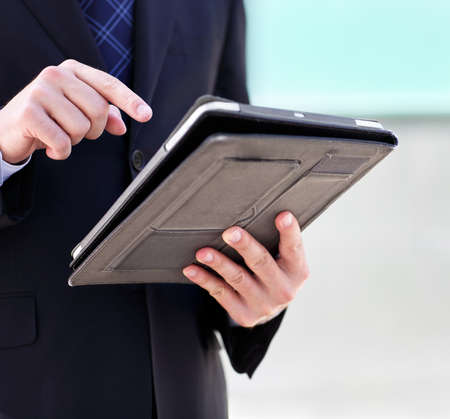 technology career: Close up of the hands of the businessman with a tablet PC. Outdoors