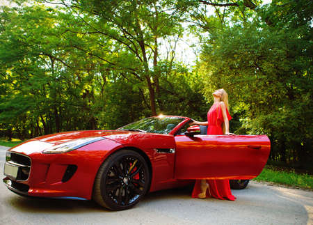 Beautiful blond young woman standing near a sports car in a long red dress