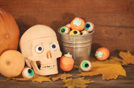 pumpkin face: Creepy skull, halloween sweets and pumpkins for Halloween party