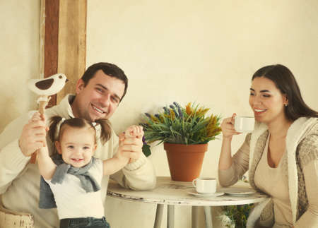 rural home: Happy smiling family with one year old baby girl drinking coffee indoor Stock Photo