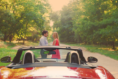 Young happy couple standing near red car. Copy space photo