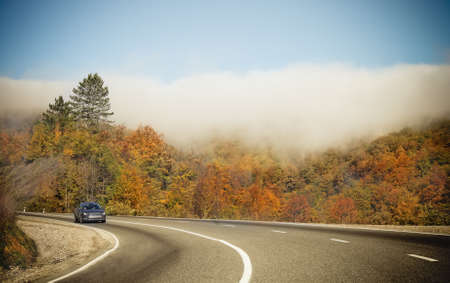 road autumnal: Foggy autumnal mountain road with lonely car Stock Photo