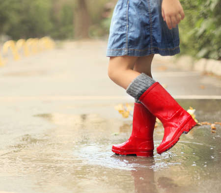 puddle: Child wearing red rain boots jumping into a puddle. Close up Stock Photo