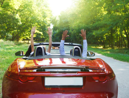 Happy free couple driving in red retro car cheering joyful with arms raised. Road trip travel concept photo
