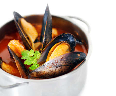 nether: Copper pot of gourmet mussels isolated on white garnished with fresh herbs for a tasty seafood meal Stock Photo