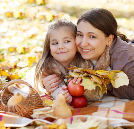 Happy young mother with little daughter in autumn park photo