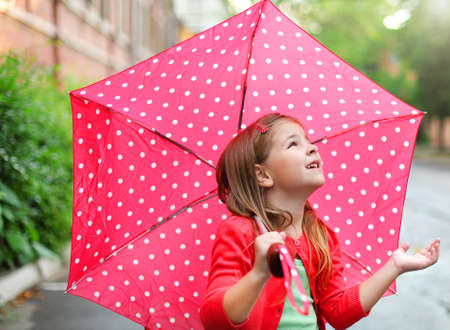 Child with polka dots umbrella wearing red rain boots jumping into a puddle Stock Photo