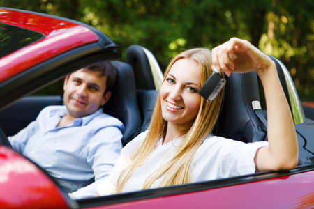 Couple in red cabriolet in a sunny day. Woman holding key photo