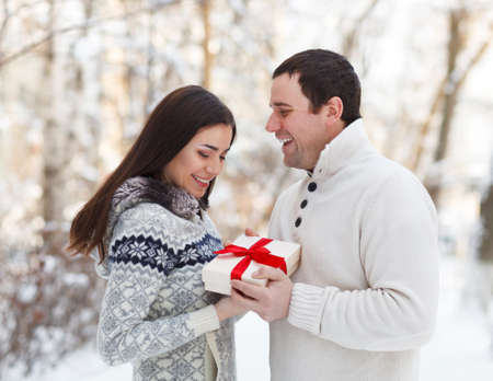 Happy young couple in love with present having fun in the winter park photo