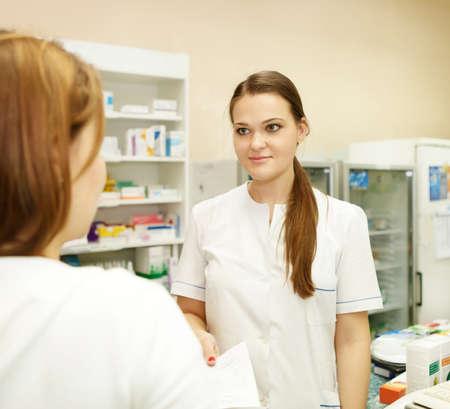 suggesting: Pharmacist suggesting medical drug to buyer in pharmacy drugstore Stock Photo