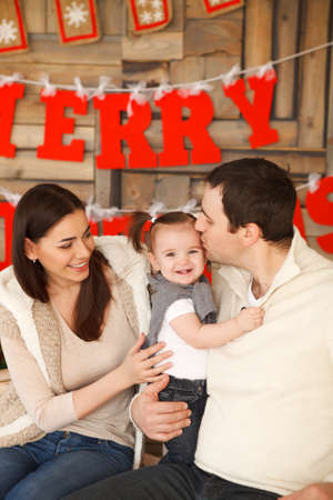 baby christmas: Happy smiling family with near the Christmas background Stock Photo