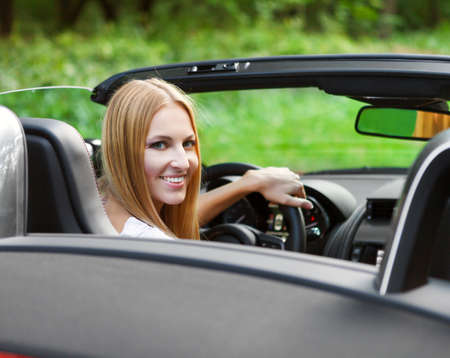 convertible car: Beautiful blond young woman driving a sports car