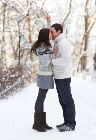beso: Feliz pareja de j�venes bajo el mu�rdago se divierten en el parque de invierno