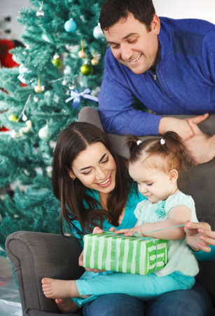 holding family together: Happy family with Christmas present near the Christmas tree