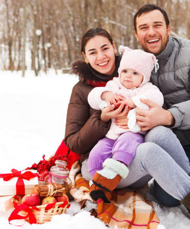 winter day: Happy smiling family with at the winter picnic outdoors
