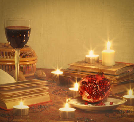 Holiday still life with pomegranate, red wine, books and candles photo