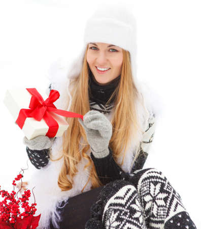 Young smiling woman holding gift decorated with red ribbon outdoors. Winter time photo