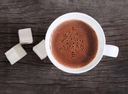 chocolate caliente: Taza de chocolate caliente o chocolate con malvaviscos decorado por el árbol de Navidad
