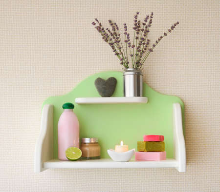 Decorative shelf on the wall with lavender flowers in vase and cosmetics on it photo