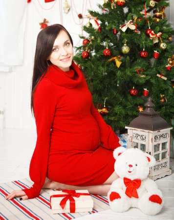 Happy young pregnant woman sitting near the Christmas tree  photo