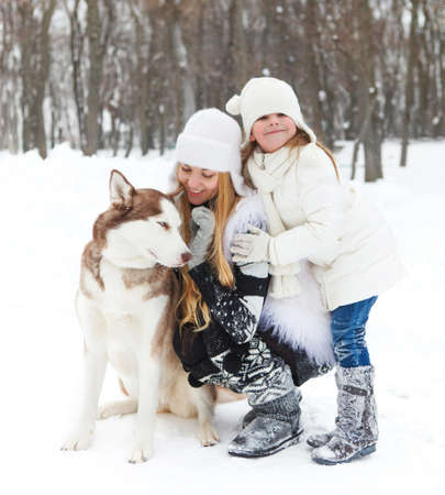 Happy young mother with daughter in the winter park with huskies dog photo