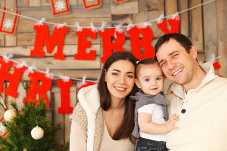 portrait couple: Happy smiling family with near the Christmas background Stock Photo