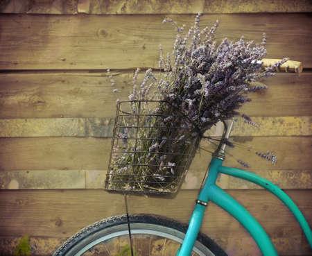 retro bicycle: Vintage bicicleta con cesta de flores de lavanda cerca de la pared de madera