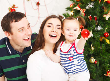 Happy smiling family near the Christmas tree Stock Photo - 22810089