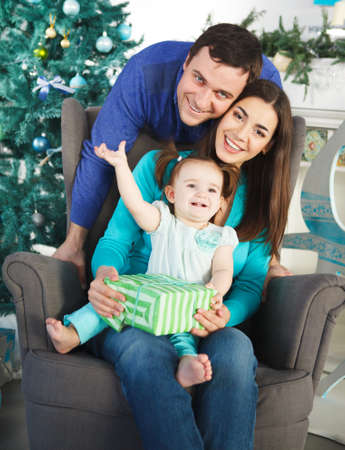 purpule: Happy family with Christmas present near the Christmas tree