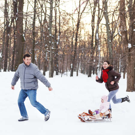Young happy family in winter park. Baby on the sled In the snow Stock Photo - 22847047