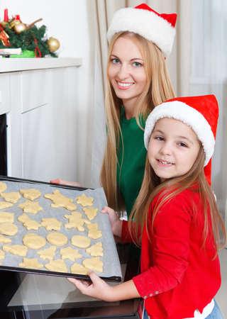 weihnachtskuchen: Kleines Mädchen mit ihrer Mutter Plätzchen Backen am Küchentisch